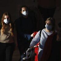 Illustrative: Travelers wearing protective masks arrive at Ben Gurion Airport, Feb. 27, 2020. (AP Photo/Ariel Schalit)