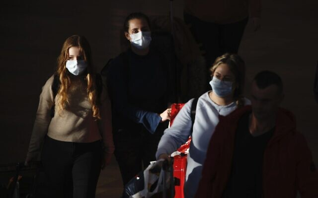 Illustrative: Travelers wearing protective masks arrive at Ben Gurion Airport, Feb. 27, 2020. (AP Photo/Ariel Schalit)