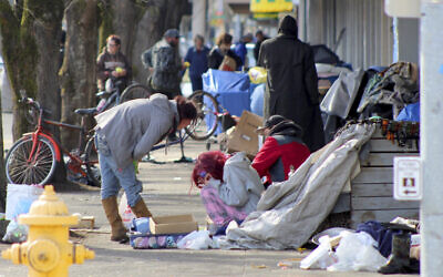 In this March 3, 2020, photo, homeless people crowd a sidewalk in downtown Salem, Oregon, where they have set up a makeshift camp. (AP Photo/Andrew Selsky)