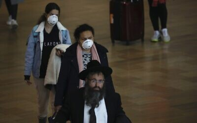 Passengers wearing masks to help protect against coronavirus arrive at the Ben Gurion airport near Tel Aviv on March 10, 2020. (AP Photo/Ariel Schalit)