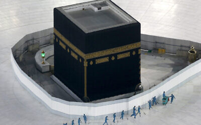 Workers disinfect the ground around the Kaaba, the cubic building at the Grand Mosque, in the Muslim holy city of Mecca, Saudi Arabia, March 7, 2020. (AP Photo/Amr Nabil)