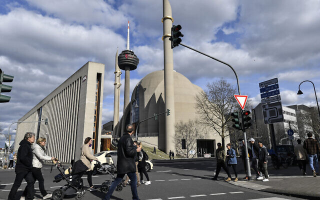 People near the German central DITIB mosque in Cologne, Germany, March 15, 2020, after the city banned religious services due to the coronavirus outbreak.  (AP Photo/Martin Meissner)