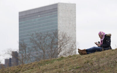 A woman listens to music at a park on Roosevelt Island, Tuesday, March 17, 2020, in New York, with a United Nations building in the background. (AP/Mary Altaffer)