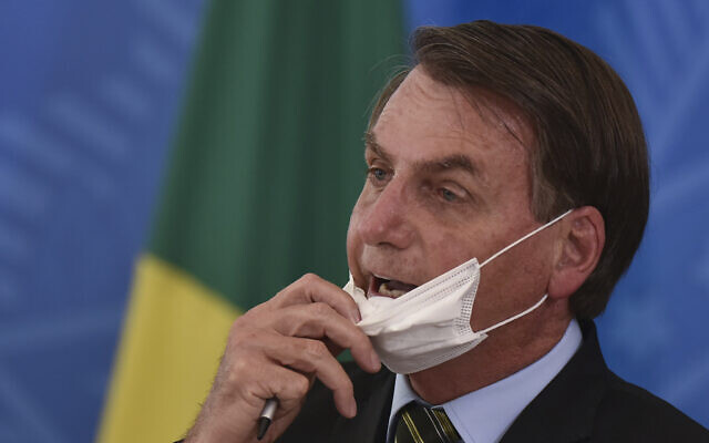 Brazil's President Jair Bolsonaro removes his mask to speak to journalists after a press conference on the new coronavirus, at the Planalto Presidential Palace in Brasilia, Brazil on March 18, 2019. (AP/Andre Borges)