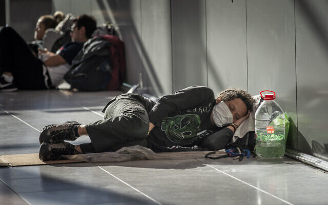 A passenger sleeps at Ezeiza International Airport in Buenos Aires, Argentina, on Monday, March 23, 2020. Many Argentines who returned from overseas struggle to get to their local destination amid travel restrictions put in place to help stop the spread of the new coronavirus. (AP Photo/Victor R. Caivano)