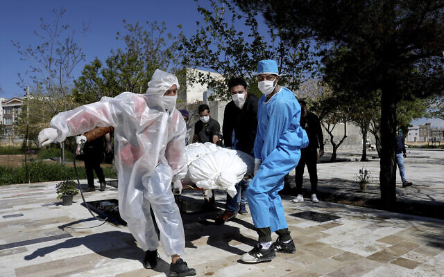 People wearing protective clothing carry the body of a victim who died after being infected with the new coronavirus at a cemetery just outside Tehran, Iran, Monday, March 30, 2020.  (AP Photo/Ebrahim Noroozi)