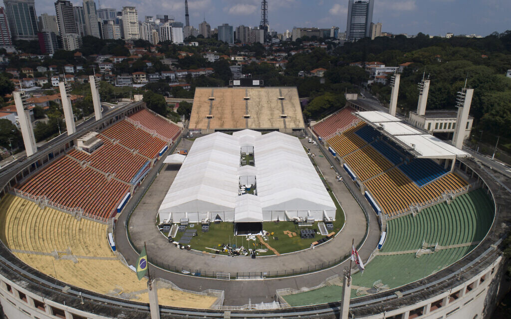 Workers set up a temporary field hospital to treat patients who have COVID-19 inside Pacaembu stadium in Sao Paulo, Brazil, Monday, March 30, 2020. (AP Photo/Andre Penner)