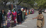 An Indian policewomen urges migrants to maintain social distance while standing in a queue to collect handouts given by the Telangana government during lockdown to prevent the spread of new coronavirus in Hyderabad, India, Tuesday, March 31, 2020.  (AP Photo/Mahesh Kumar A.)