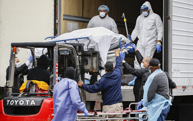A body wrapped in plastic is unloaded from a refrigerated truck and handled by medical workers wearing personal protective equipment due to COVID-19 concerns, March 31, 2020, at Brooklyn Hospital Center in the Brooklyn borough of New York (AP Photo/John Minchillo)
