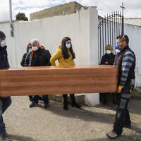 Undertakers carry the coffin of Rosalia Mascaraque, 86, during the coronavirus outbreak in Zarza de Tajo, central Spain, on April 1, 2020. . (AP Photo/Bernat Armangue)