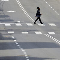 An ultra-Orthodox man crosses a main deserted street in Bnei Brak on  April 2, 2020. (AP Photo/Ariel Schalit)