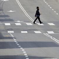 An ultra-Orthodox man crosses a main deserted street in Bnei Brak on Thursday, April 2, 2020. (AP Photo/Ariel Schalit)