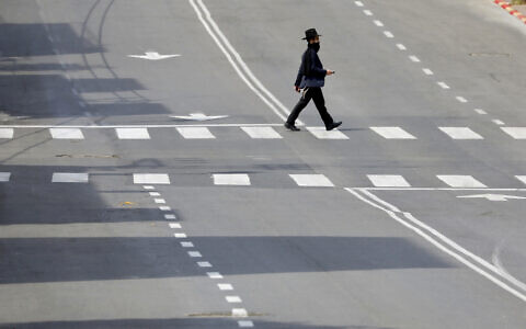 An ultra-Orthodox man crosses a main deserted street in Bnei Brak on Thursday, April 2, 2020. (AP Photo/Ariel Schalit)