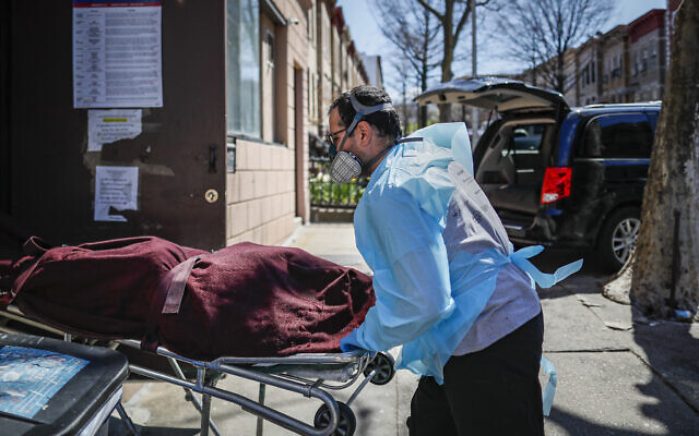 Employees deliver a body at Daniel J. Schaefer Funeral Home, Thursday, April 2, 2020, in the Brooklyn borough of New York.  (AP/John Minchillo)