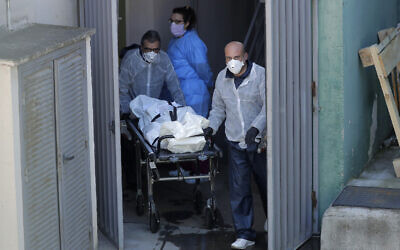 Funeral home workers carry a body from the Vitalia nursing home in Leganes, Spain, April 3, 2020. (AP Photo/Manu Fernandez)
