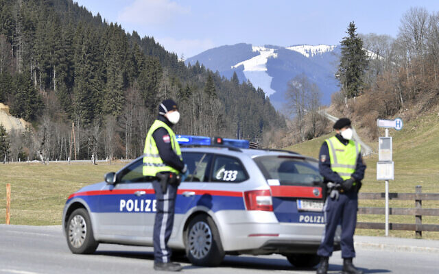 Police officers block the road to the skiing resort Saalbach Hinterglemm in  Austrian province of Salzburg, Friday, April 3, 2020 after the city was quarantined. (AP Photo/Kerstin Joensson)