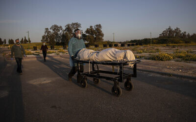 A member of Hevra Kadisha, an organization which prepares bodies of deceased Jews for burial according to Jewish tradition, pushes a body during a funeral of a Jewish man who died from coronavirus in the costal city of Ashkelon, Israel, April 2, 2020. (AP Photo/Tsafrir Abayov)