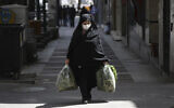A woman wearing a face mask to protect against the new coronavirus carries her shopping in northern Tehran, Iran, Saturday, April 4, 2020. (AP Photo/Vahid Salemi)