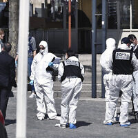 Police officers investigate after a man wielding a knife attacked residents venturing out to shop in the town under lockdown, Saturday April 4, 2020 in Romans-sur-Isere, southern France. (AP)