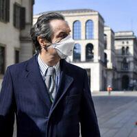 The governor of Region Lombardy, the coronavirus worst-hit region of Italy, Attilio Fontana wears a face mask as he walks in Milan, Italy, April 5, 2020. (Claudio Furlan/LaPresse via AP)