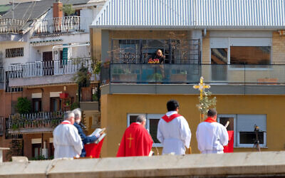 A faithful from a facing balcony follows the celebration of the Palm Sunday mass on the roof of the church of San Pio X, in Rome, Sunday, April 5, 2020. Churches are closed to faithful all over Italy due to the coronavirus outbreak. (Mauro Scrobogna/LaPresse via AP)