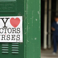 A sign acknowledging the work of doctors and nurses is posted on a traffic control box outside Brooklyn Hospital Center, as a hospital worker, right, waits for a traffic light to change before reporting to duty, Sunday, April 5, 2020, in New York. The Brooklyn hospital is one of several in the area treating high numbers of coronavirus patients. (AP Photo/Kathy Willens)