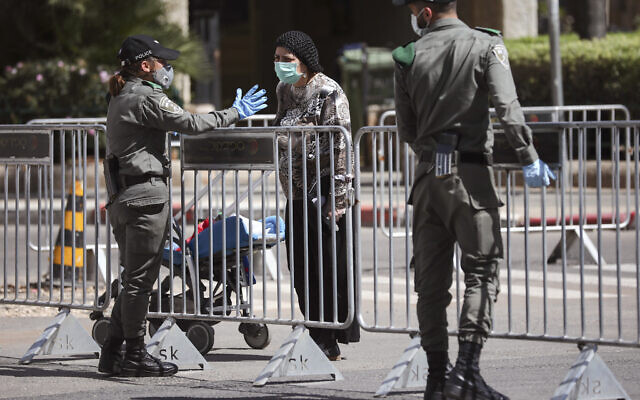 Illustrative: Border police officers block a main road following the government's measures to help stop the spread of the coronavirus, in Bnei Brak, on April 3, 2020. (AP Photo/Oded Balilty,)