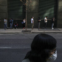 People wait in line to collect unemployment insurance, many of them affected by the economic crisis triggered by the spread of the new coronavirus, in downtown Chile on April 6, 2020. (AP/Esteban Felix)
