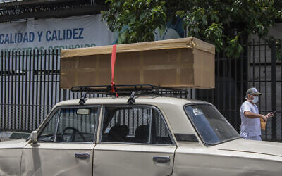 A cardboard coffin with a body sits on the roof rack of a car before it is taken away to be buried, outside the Teodoro Maldonado Hospital in Guayaquil, Ecuador, Monday, April 6, 2020. (AP Photo/Luis Perez)