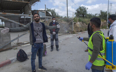 In this Tuesday, April 7, 2020 photo, a paramedic from the Palestinian Ministry of Health disinfects Palestinian laborers to help contain the coronavirus, as they exit an Israeli army checkpoint after returning from work in Israel, near the West Bank village of Nilin, west of Ramallah.  (AP Photo/Nasser Nasser)