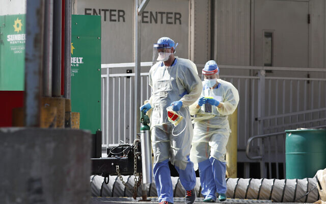 Medical personnel carry an oxygen tank into Elmhurst Hospital Center's emergency room after inspecting it outdoors, April 7, 2020, in New York during the current coronavirus outbreak. (AP Photo/Kathy Willens)