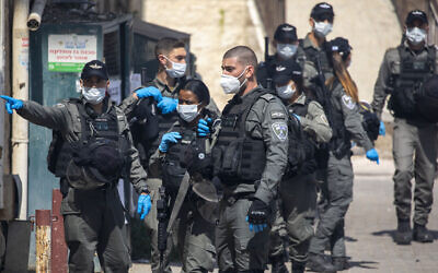 Israeli border police officers wearing face mask gather after dispersing ultra-Orthodox Jewish children burning leavened items in final preparation for the Passover holiday in the Orthodox neighborhood of Mea Shearim in Jerusalem, Wednesday, April 8, 2020. (AP Photo/Ariel Schalit)