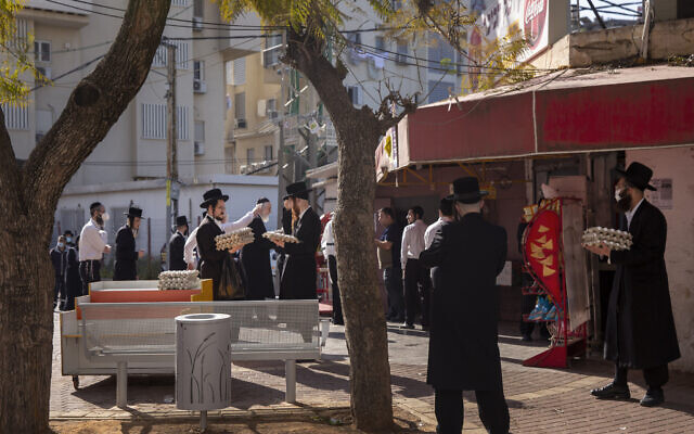Ultra-Orthodox Jews some wearing face masks line up to buy eggs, in Bnei Brak, Israel, Wednesday, April 8, 2020. (AP/Oded Balilty)