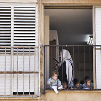 An ultra-Orthodox man prays the morning prayer in his apartment as his children look through the window during a lockdown imposed to slow the spread of the coronavirus, in Bnei Brak, April 8, 2020 (AP Photo/Oded Balilty)
