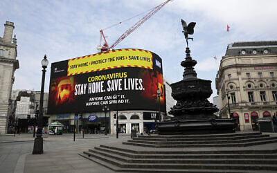 A video screen displays a message urging people to stay home in a nearly deserted Piccadilly Circus in London, Wednesday, April 8, 2020. (AP Photo/Matt Dunham)