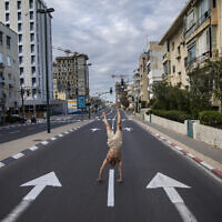 An Israeli man stands on his hands on an empty road during a lockdown following government measures to help stop the spread of the coronavirus, in Tel Aviv, April 8, 2020. (AP Photo/Oded Balilty)