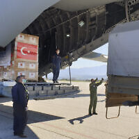 In this handout photo provided by the Turkish Defense Ministry, North Macedonian officials unload Personal Protection Equipment donated by Turkey to help the country combat the  coronavirus outbreak,  April 8, 2020.  (Turkish Defence Ministry via AP)
