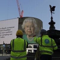 An image of Britain's Queen Elizabeth II and quotes from her historic television broadcast commenting on the coronavirus pandemic are displayed on a big screen behind the Eros statue at Piccadilly Circus in London, April 9, 2020. (AP Photo/Kirsty Wigglesworth)