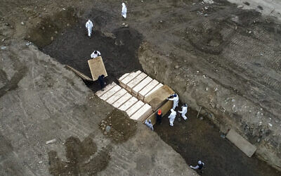 Workers wearing personal protective equipment bury bodies in a trench on Hart Island,  April 9, 2020, in the Bronx borough of New York amid the mounting death toll from the coronavirus outbreak. (AP Photo/John Minchillo)