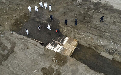 Workers wearing personal protective equipment bury bodies in a trench on Hart Island, Thursday, April 9, 2020, in the Bronx borough of New York.  (AP Photo/John Minchillo)