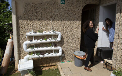 Volunteer Einat Kedem, left, speaks with emergency room doctor Maayan Bacher after delivering her a home-cooked meal, in the Israeli city of Raanana, April 6, 2020 (AP Photo/Sebastian Scheiner)