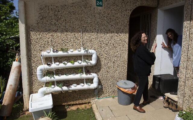 Volunteer Einat Kedem, left, speaks with emergency room doctor Maayan Bacher after delivering her a home-cooked meal, in the Israeli city of Raanana, April 6, 2020 (AP Photo/Sebastian Scheiner)