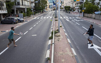 File: Israelis play tennis on an empty road during lockdown following the government's measures to help stop the spread of the coronavirus, in Ramat Gan, near Tel Aviv, April 9, 2020. (AP Photo/Oded Balilty)