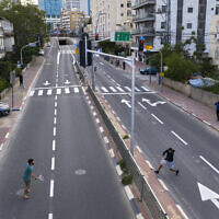 Israelis play tennis on an empty road during lockdown, following the government's measures to help stop the spread of the coronavirus, in Ramat Gan, near Tel Aviv, Israel, April 9, 2020. (AP/ Oded Balilty)