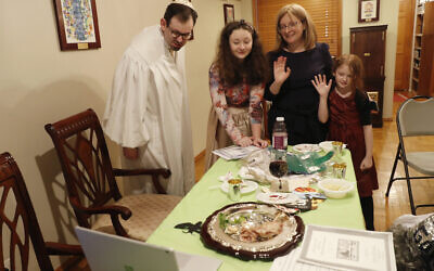 Rabbi Shlomo Segal, left, and his family wave goodbye to participants after he conducted a virtual Passover seder for members of his congregation, friends and family and broadcast it on YouTube and internet dial-in connections from his home in the Sheepshead Bay section of Brooklyn during the current coronavirus outbreak, Wednesday, April 8, 2020, in New York. From left, are Segal, daughter Shira, 12, wife Adina and daughter Rayna, 8. (AP/Kathy Willens)
