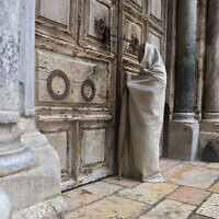 A Christian worshiper stands at the closed door of the Church of the Holy Sepulchre, believed by many Christians to be the site of the crucifixion and burial of Jesus Christ, in Jerusalem, April 10, 2020 (AP Photo/Sebastian Scheiner)