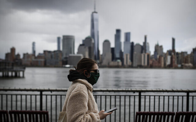 The downtown New York City skyline looms over pedestrians wearing masks due to COVID-19 concerns, Friday, April 10, 2020, in Jersey City, NJ (AP Photo/John Minchillo)