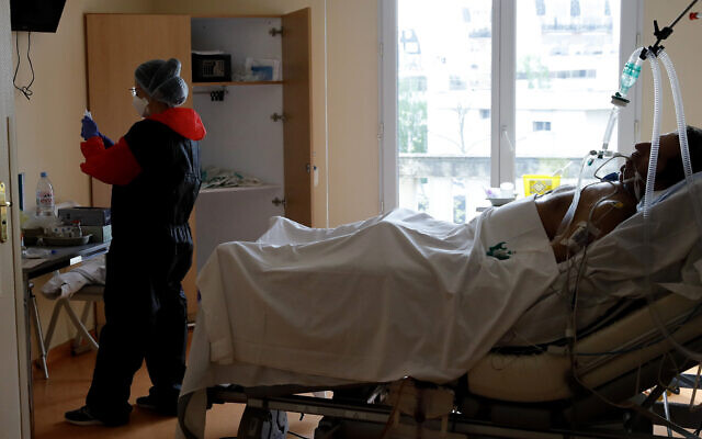 A medic takes care of a patient affected by COVID-19 virus in the ICU unit at the Ambroise Pare clinic in Neuilly-sur-Seine, near Paris, April 10, 2020 (AP Photo/Christophe Ena)