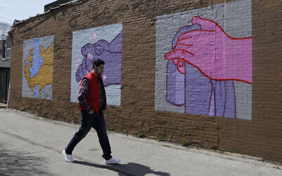 A man walks by a mural depicting hand washing in Logan Square by artist James Mosher, Saturday, April 11, 2020 in Chicago. (AP Photo/Nam Y. Huh)