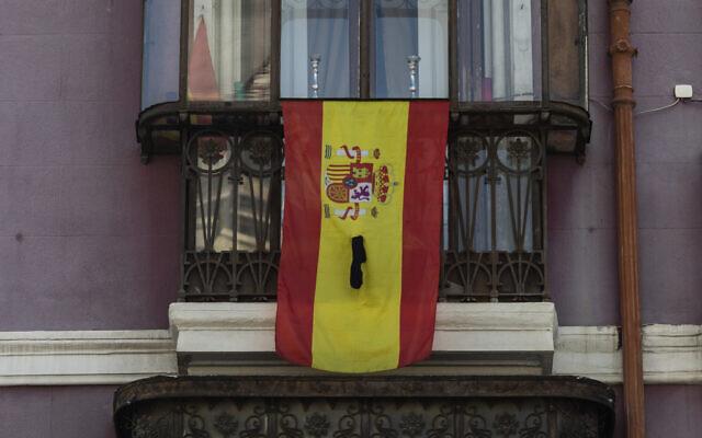 A Spanish flag on a window ledge with a black ribbon in Madrid,  April 12, 2020. (AP Photo/Bernat Armangue)